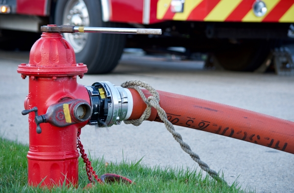 A fire hydrant with a hose attached