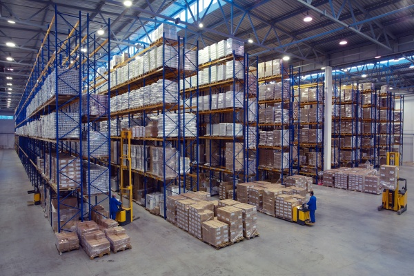 The interior of a large goods warehouse with shelves of pallet rack system storage.