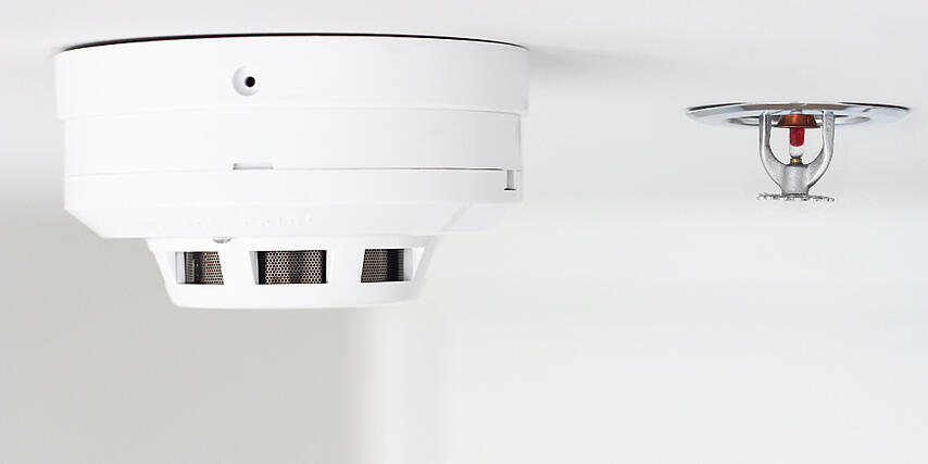 A smoke alarm and fire sprinkler head mounted to a ceiling