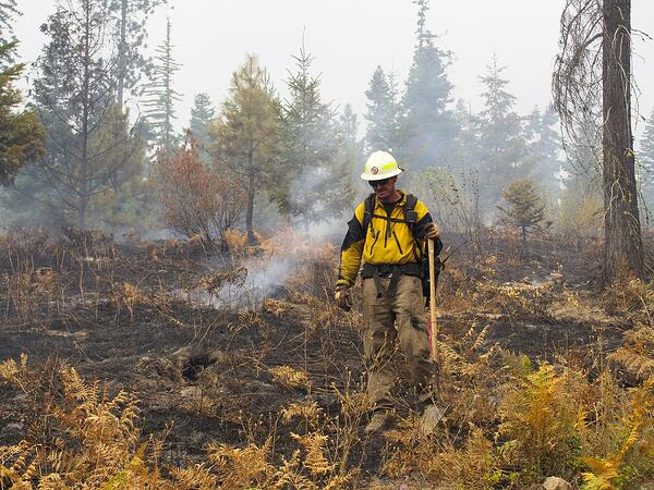 A firefighter monitors a controlled burn