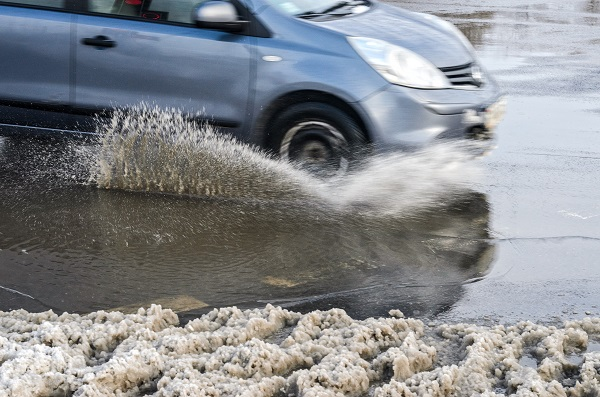 A car driving through a puddle surrounded by melting snow