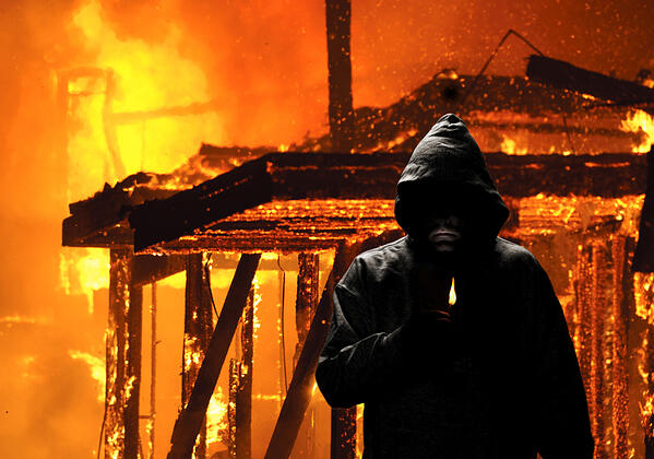 A hooded person walking away from an arson fire.