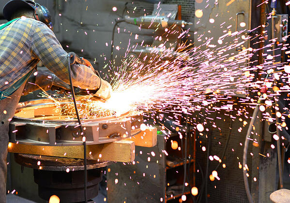 A manufacturing worker with equipment creating many sparks near wood