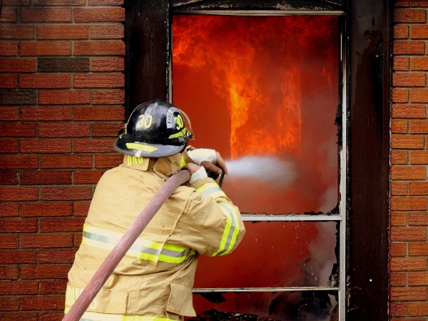 A firefighter spraying water through a doorway at flames