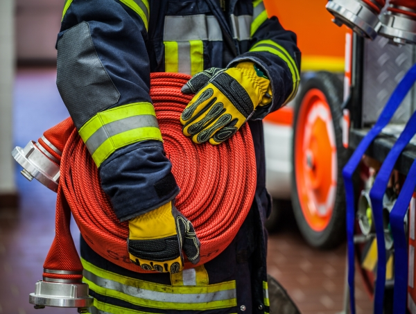 A firefighter carries a hose and nozzle
