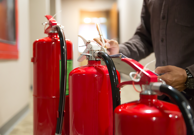 A person checks fire extinguishers for recent inspection and maintenance
