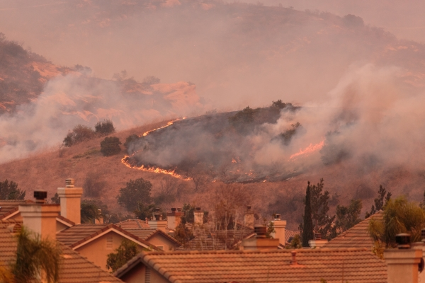 Wildfire burning vegetation on a hill behind houses