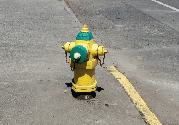 Fire hydrant with yellow body and green top and nozzle cap