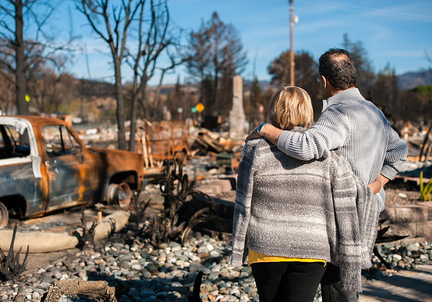 A couple surveys homes burned by a wildfire
