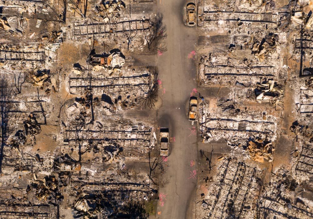 An aerial view of a neighborhood destroyed by a wildfire