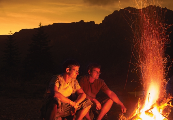 Two men sitting next to a campfire