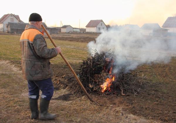 Man burning debris in a field