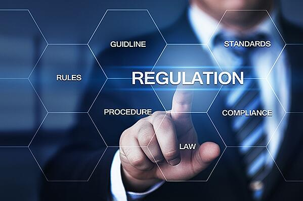 "A man stands in front of a board with the words ""regulation,"" ""procedure"" and other terms on it."